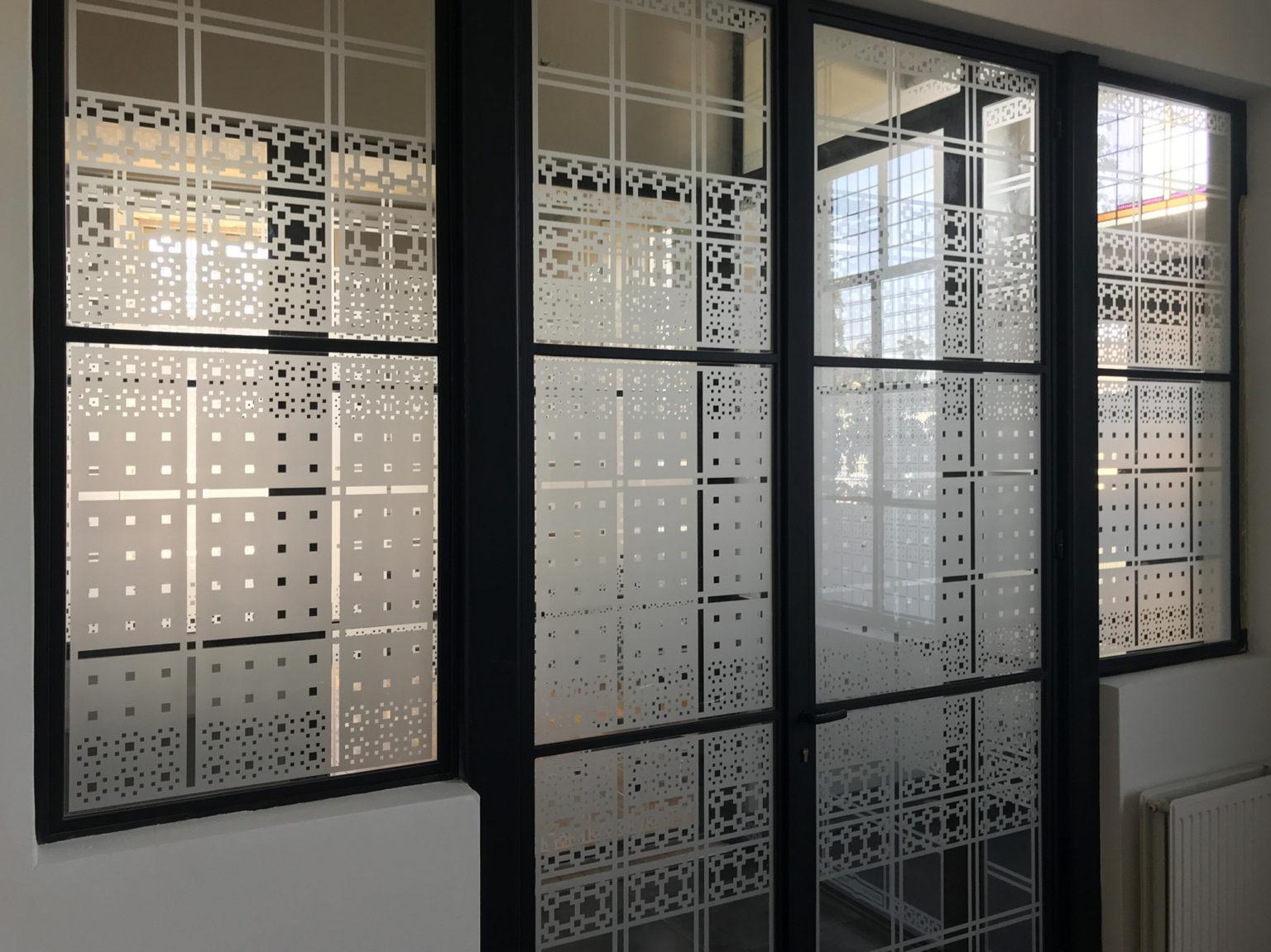 Zicht vanuit kantoor op entree kantoorvilla met raamfolie patroon
