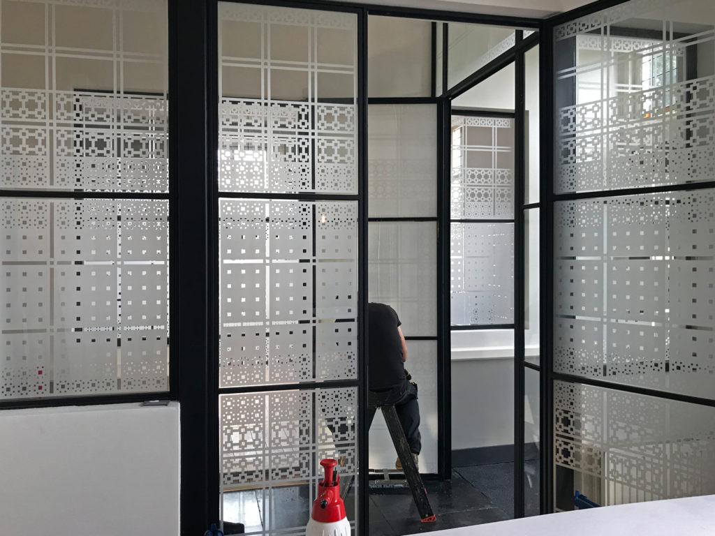 aanbrengen raamfolie patroon kantoor